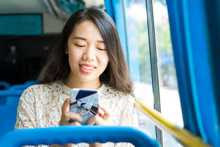 Asian girl using phone on public bus