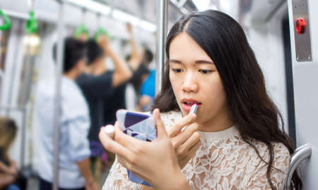 Asian girl fixing make up on subway ride Stok Fotoğraf - 82753751