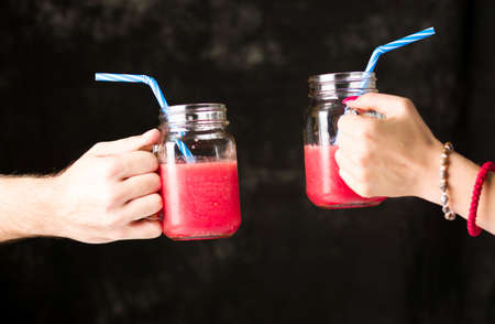 People clinking  glasses with healthy watermelon smoothie