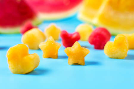 triangle shaped: Shaped yellow and red watermelon slices on blue background Stock Photo