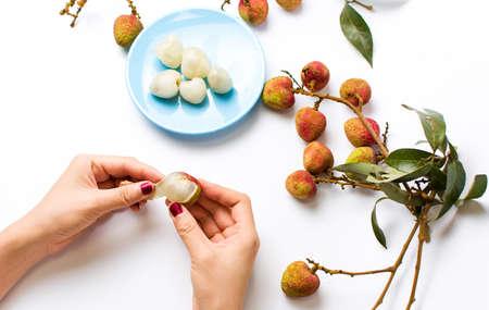 Female hands peeling lychee fruit on white
