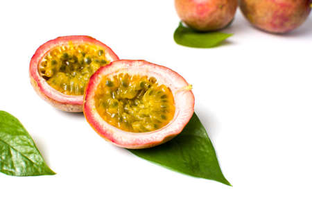 Halved passion fruit with leaves isolated on white