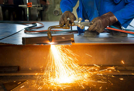 Man cutting metal with fire from a welding cutting torch