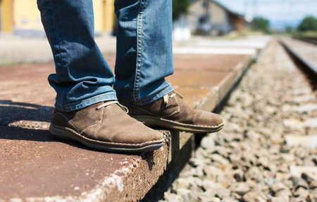 Man waiting for a train wearing vintage leather shoes