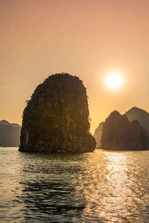 Romantic Halong bay sunset over limestone rocks in Vietnam