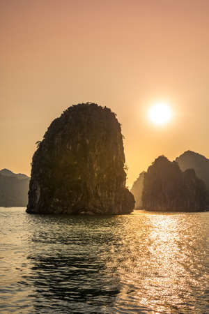 Romantic Halong bay sunset over limestone rocks in Vietnam