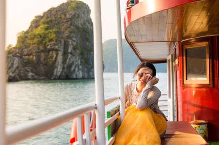 Girl enjoying the last sunshine on a cruise boat