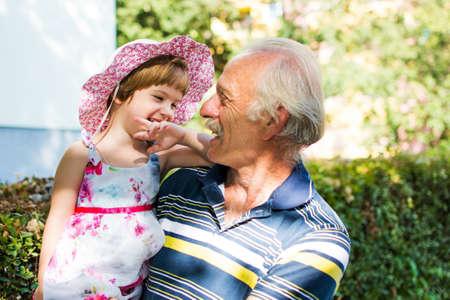 おじいちゃんと屋外に笑って彼の 3 歳の孫娘 写真素材