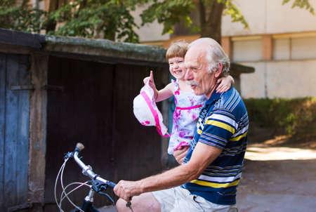彼の手の孫娘と祖父乗馬自転車 写真素材