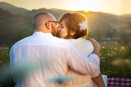 Couple kissing on picnic with romantic sunset view