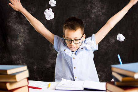 Boy throws away papers with homework assignment failure Stock Photo