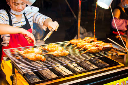 NANNING, CHINA - JUNE 9, 2017: Chinese chef preparing barbecue on the Zhongshan Snack Street, a food market in Nanning. This food street is the biggest night food market  in the capital city of Guangxi province in China