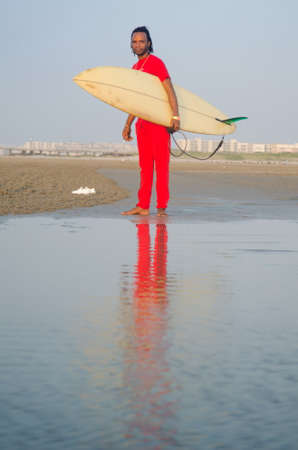 Man holding a surfboard on the beach with calm seaside Stock Photo