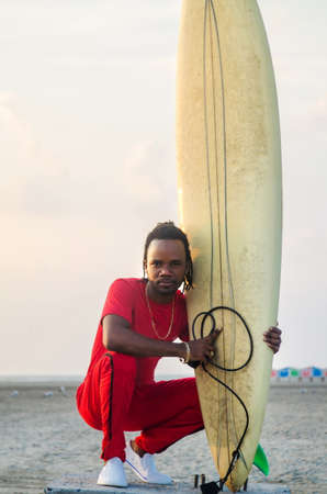 jamaican man: African American man with surfboard on the beach