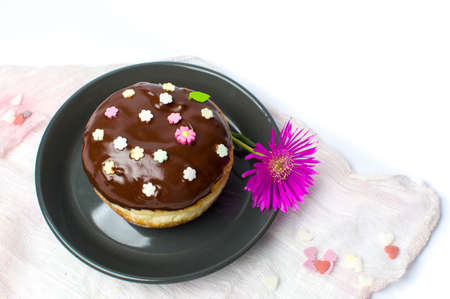 Decorated chocolate donuts with purple flower on a plate Stock Photo
