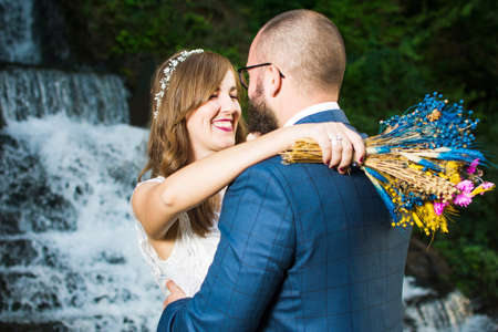 Wedding couple hugging in front of a waterfall Stock Photo
