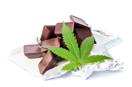 Marijuana leaf with chocolate cubes on white background Фото со стока