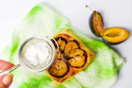 Adding sugar to plum sweet pie slice Stock Photo