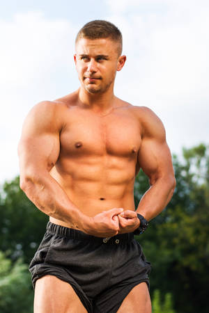 Young bodybuilder showing shaped muscles outdoors