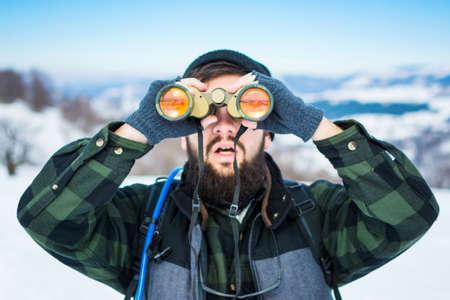 Man using binoculars on a snow covered mountain