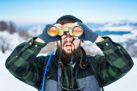 Man using binoculars on a snow covered mountain