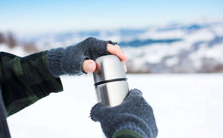 Man using thermos bottle on the snowy mountain Stock Photo
