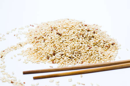 Yellow rice on a pile and wooden chopsticks on white Stock Photo