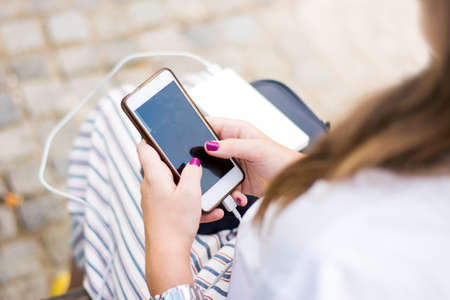 Girl using smart phone while charging on the power bank Stok Fotoğraf - 86368532