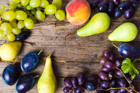 素朴な木製の背景トップビュー上の各種の果物