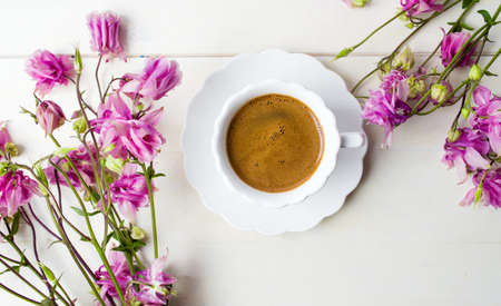 Cup of coffee on a table decorated with purple flowers Stock Photo