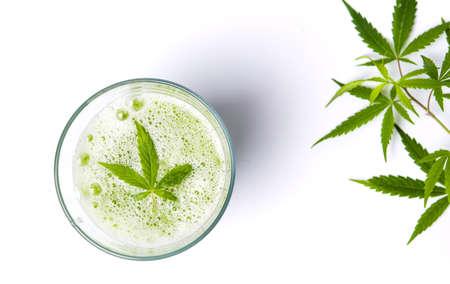 白い背景の上の緑のマリファナのスムージー ジュース