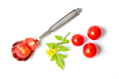 Sliced cherry tomato in a spoon with natural branch isolated Stock Photo