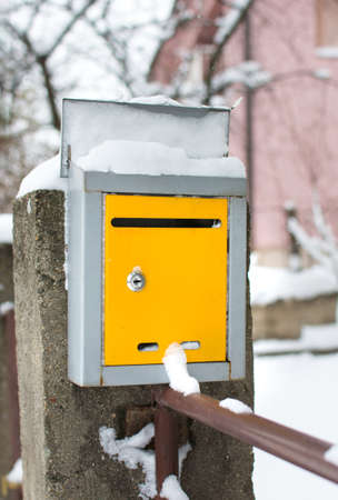 Snow covered yellow mailbox in front of a house