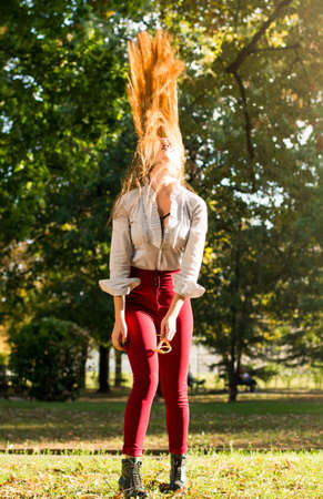 wind blown: Girl swinging her long hair in the park Stock Photo