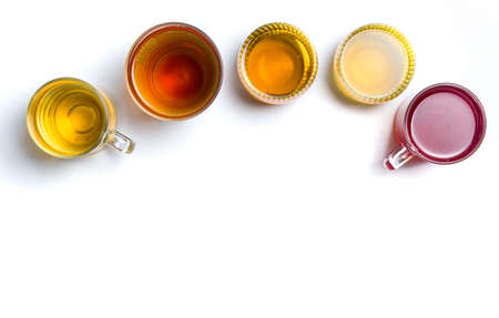 Various herbal teas in glass cups on white background