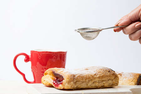 Female hand adding sugar to puff pastry against white background Stock Photo