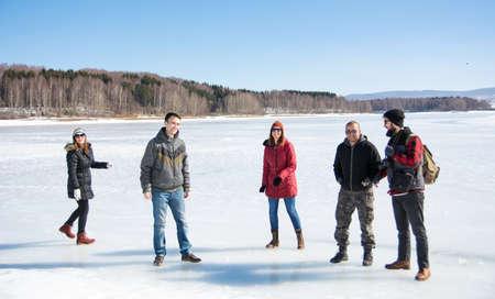Group of friends having fun on a frozen lake