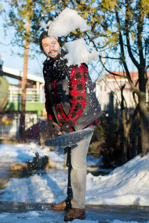 bearded man shoveling snow wearing a shirt and a west Stock Photo
