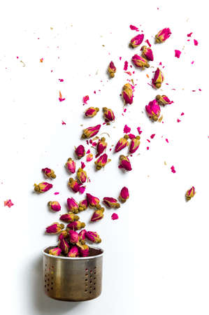 Rose tea flowers flying out of kettle colander on white background