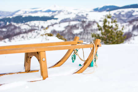 Wooden sleds on snow covered mountain top