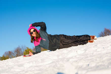 Girl laying on snow covered mountain in ski jacket