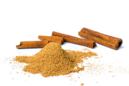 Cinnamon powder and sticks isolated on white background Stock Photo