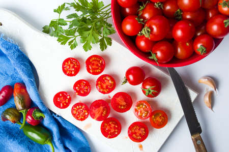 Cherry tomatoes sliced on a white cutting board Stock Photo