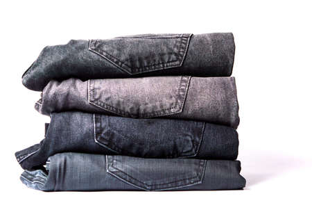 Pile of gray jeans isolated on white background