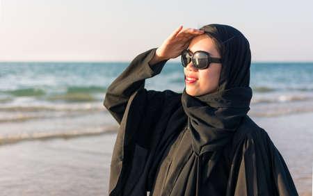 Portrait of a woman wearing abaya on the beach Stock Photo