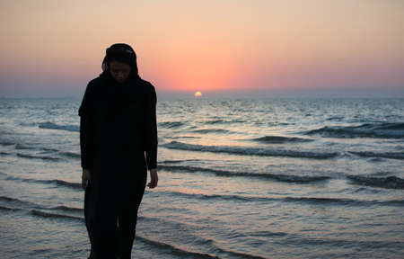 Woman in abaya on the beach at sunset time Stock Photo