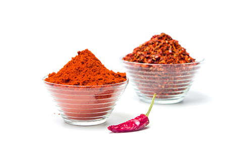Smashed and ground red pepper powder in a glass bowl isolated