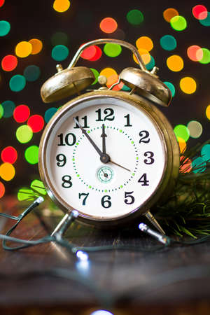 Vintage clock approaching midnight and festive Christmas lights