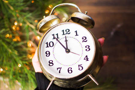 Hand holding Vintage clock approaching midnight and festive Christmas lights