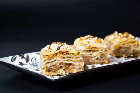 Baklava dessert slices with nuts on dark background Imagens